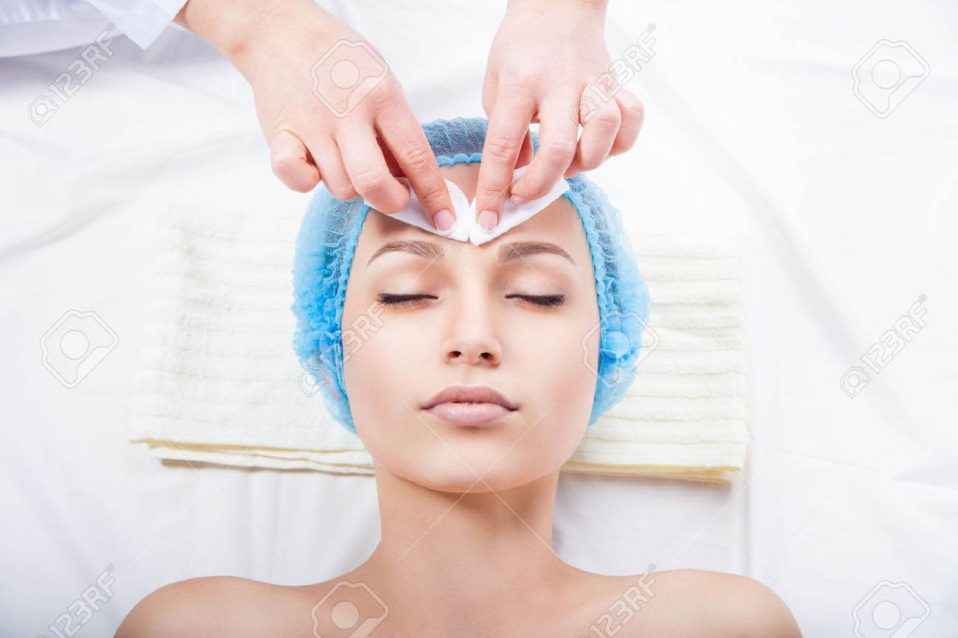 32954684-skin-care-woman-cleaning-face-by-beautician-over-white-background